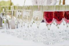 Exponeringsglas av rött och vitt vin på en tabell Många glass vin i rad på den vita bordduken Royaltyfri Foto