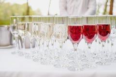 Exponeringsglas av rött och vitt vin på en tabell Många glass vin i rad på den vita bordduken Royaltyfria Bilder
