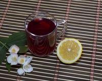Exponeringsglas av rött te med en citron på en filt Royaltyfri Fotografi
