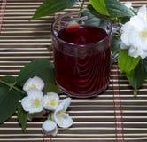 Exponeringsglas av rött te på en filt med en blomma Royaltyfria Foton