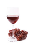 Exponeringsglas av rött vin bredvid en filial av druvor Royaltyfri Bild