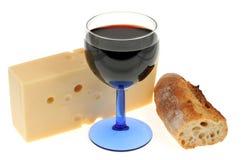 Exponeringsglas av rött vin, emmental och bröd på en vit bakgrund royaltyfri foto