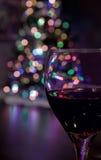 Exponeringsglas av rött vin framme av julgranen Royaltyfri Fotografi