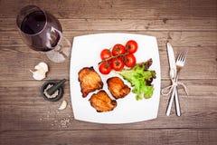 Exponeringsglas av rött vin, grillat kött på den vita plattan, tomater, le Royaltyfri Foto