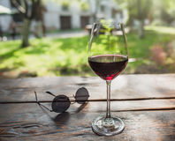 Exponeringsglas av rött vin i framdelen av sommargården Royaltyfri Bild
