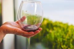 Exponeringsglas av rött vin i handen på avsmakningen arkivbilder