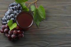 Exponeringsglas av rött vin med blåa druvor och det gröna bladet på den mörka trätabellen Bästa sikt med kopieringsutrymme Arkivbilder