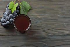Exponeringsglas av rött vin med blåa druvor och det gröna bladet på den mörka trätabellen Bästa sikt med kopieringsutrymme Arkivfoton