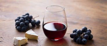 Exponeringsglas av rött vin med den ny druvan och ost på trätabellen royaltyfria foton