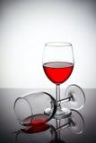 Exponeringsglas av rött vin med droppar och reflexioner på en glass tabell Arkivfoton