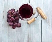 Exponeringsglas av rött vin med druvor och den gamla träkorkskruvet Royaltyfria Bilder