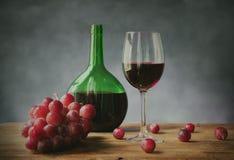Exponeringsglas av rött vin med druvor och den gröna glasflaskan royaltyfria bilder