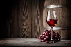 Exponeringsglas av rött vin med druvor och trumman Royaltyfri Bild