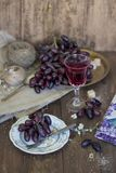 Exponeringsglas av rött vin med druvor på en träbakgrund royaltyfri bild