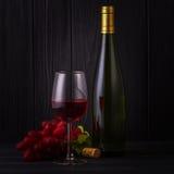 Exponeringsglas av rött vin med en flaska Arkivbild