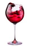 Exponeringsglas av rött vin med färgstänk som isoleras på en vit Royaltyfri Foto
