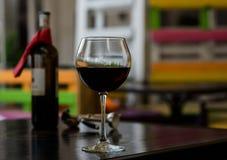Exponeringsglas av rött vin med flaskan och korkskruvet på tabellen i kafé Royaltyfria Bilder