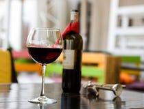 Exponeringsglas av rött vin med flaskan och korkskruvet på tabellen i kafé Fotografering för Bildbyråer