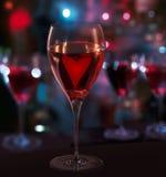 Exponeringsglas av rött vin, med hjärta. Suddigheta stadslampor Arkivbilder