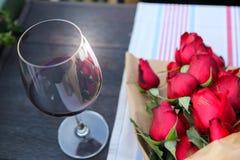 Exponeringsglas av rött vin med röda rosor Arkivbilder