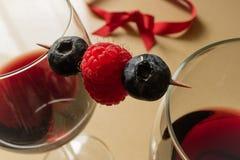 Exponeringsglas av rött vin och bär royaltyfri foto