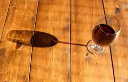 Exponeringsglas av rött vin och dess skugga på trätabellen royaltyfria foton