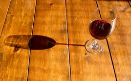 Exponeringsglas av rött vin och dess skugga på trätabellen royaltyfria bilder