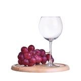 Exponeringsglas av rött vin och druvor som isoleras på vit Royaltyfri Fotografi