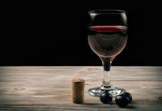 Exponeringsglas av rött vin och flaskan av vin arkivbilder