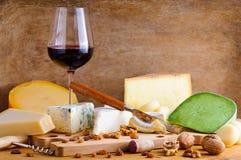 Exponeringsglas av rött vin- och ostplattan Arkivbilder