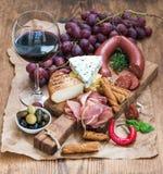 Exponeringsglas av rött vin, ost och kött stiger ombord, druvor, fikonträdet, jordgubbar, honung, brödpinnar på den lantliga trät Royaltyfri Fotografi