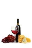 Exponeringsglas av rött vin, ostar och druvor som isoleras på en vit Arkivbilder