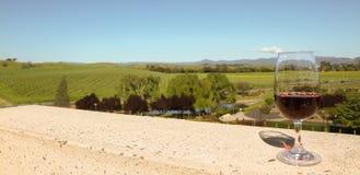 Exponeringsglas av rött vin på balkongen som förbiser Napa Valley vingårdar Arkivfoton