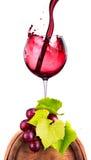 Exponeringsglas av rött vin på en trätrumma med druvan Royaltyfri Fotografi