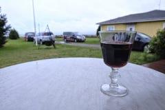 Exponeringsglas av rött vin på en våt tabell på verandan Arkivbild