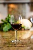 exponeringsglas av rött vin på marmorräknare med gräsplaner och blomkålen i bakgrund Fotografering för Bildbyråer