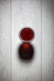 Exponeringsglas av rött vin på trätabellen. Arkivbilder
