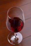 Exponeringsglas av rött vin på trätabellen close upp Arkivfoto