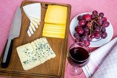 Exponeringsglas av rött vin, söta röda druvor på den vita plattan och trädtyper av skivad ost på brun träskärbräda royaltyfri bild