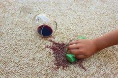 Exponeringsglas av rött vinavverkning på matta Den kvinnliga handen gör ren mattan Royaltyfri Foto