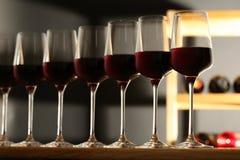Exponeringsglas av r?tt vin i k?llare royaltyfri fotografi