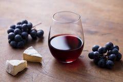 Exponeringsglas av r?tt vin med den ny druvan och ost p? tr?tabellen close upp arkivfoton