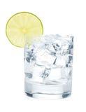 Exponeringsglas av rent vatten med iskuber och limefruktskivan Royaltyfria Bilder