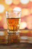 Exponeringsglas av romwhisky över defocused ljus Royaltyfri Foto