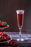 Exponeringsglas av rosa champagne på en trätabell Ställning med strawberri Arkivbild