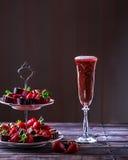 Exponeringsglas av rosa champagne på en trätabell Ställning med strawberri Royaltyfri Fotografi