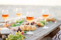 Exponeringsglas av rosa vin på picknicktabellen Arkivbilder