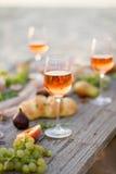 Exponeringsglas av rosa vin på picknicktabellen Royaltyfri Foto