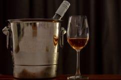 Exponeringsglas av rosa vin på trätabellen med en flaska i mer chiller hink för vin royaltyfri fotografi