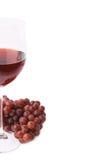 Exponeringsglas av rött vin bredvid en filial av druvor Royaltyfria Foton